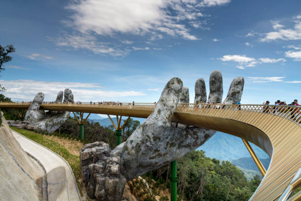 The Golden Bridge is lifted by two giant hands in the tourist resort on Ba Na Hill in Danang, Vietnam. stock photo