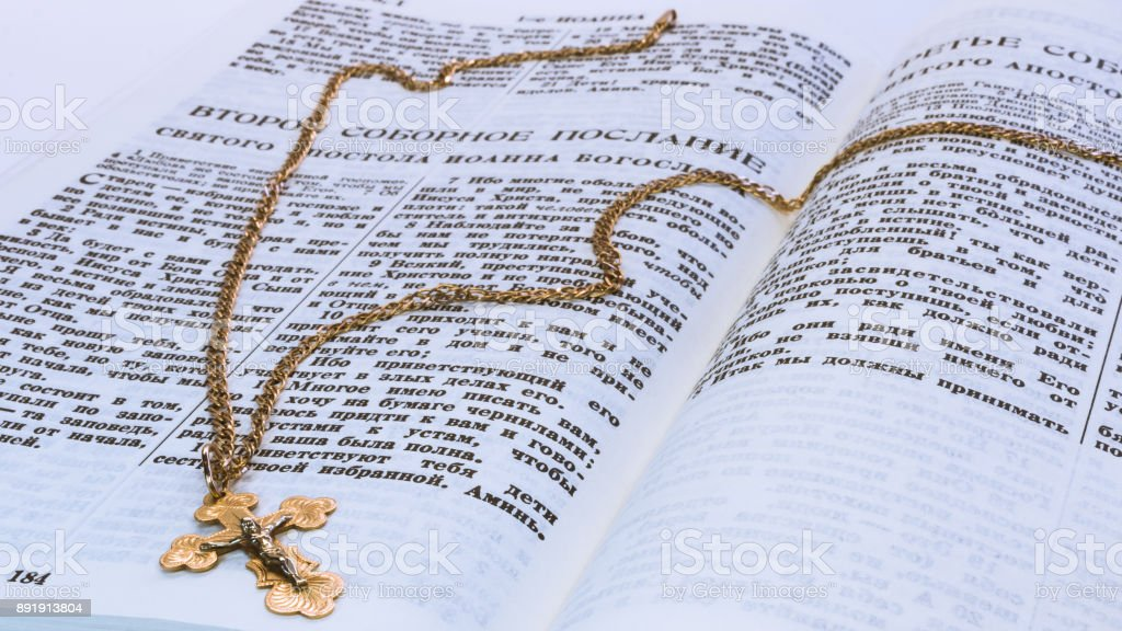 The golden cross of the crucifixion of Christ on the sacred scripture of the old covenant on the page with the text of the second catholic writings of the holy Apostle John the Theologian stock photo