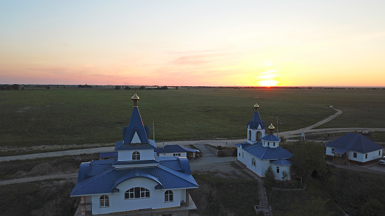 The Golden domes of the Church at sunset. Green fields with poppies all around. Orange sky and paths. Purple clouds. Countryside. Top view from a drone.
