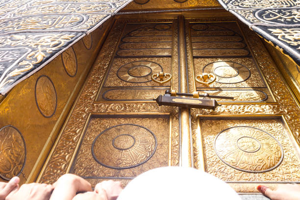The golden doors of Holy Kaaba MECCA, SAUDI ARABIA: The golden doors of the Holy Kaaba closeup, covered with Kiswah. Massive lock on the doors. Entrance to the Kaaba in Masjid al Haram umrah stock pictures, royalty-free photos & images
