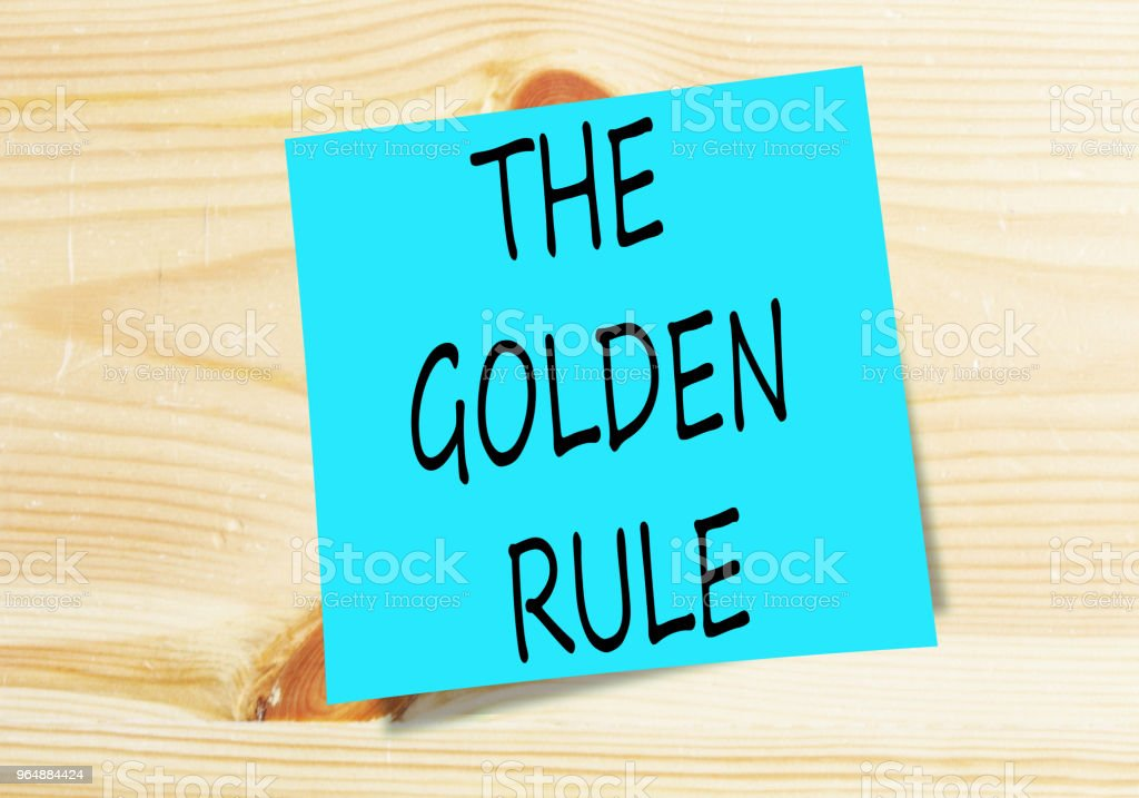 the golden rule on blue small paper on wooden background royalty-free stock photo