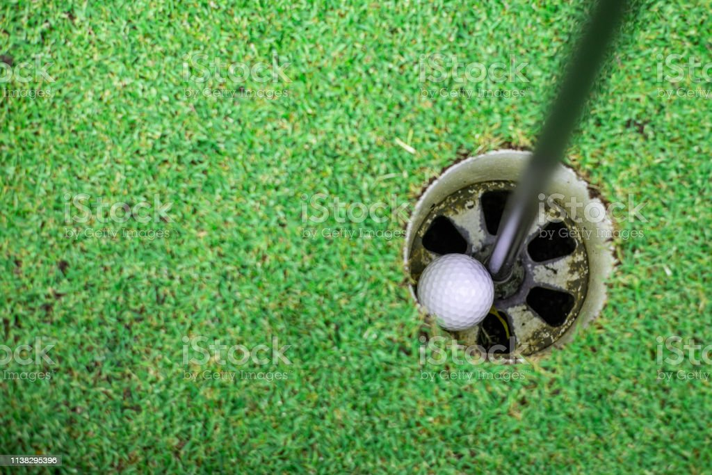 the golf ball in the golf hole.