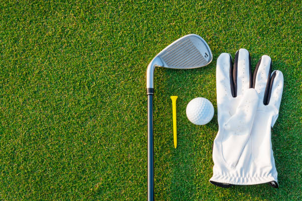The golf sport equipment  white glove ,golf ball, golf club and  yellow tee golf with green grass background. The golf sport equipment  white glove ,golf ball, golf club and  yellow tee golf with green grass background. green golf course stock pictures, royalty-free photos & images