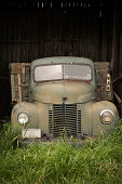A 1946 antique grain hauling truck parked in an old barn board shed.