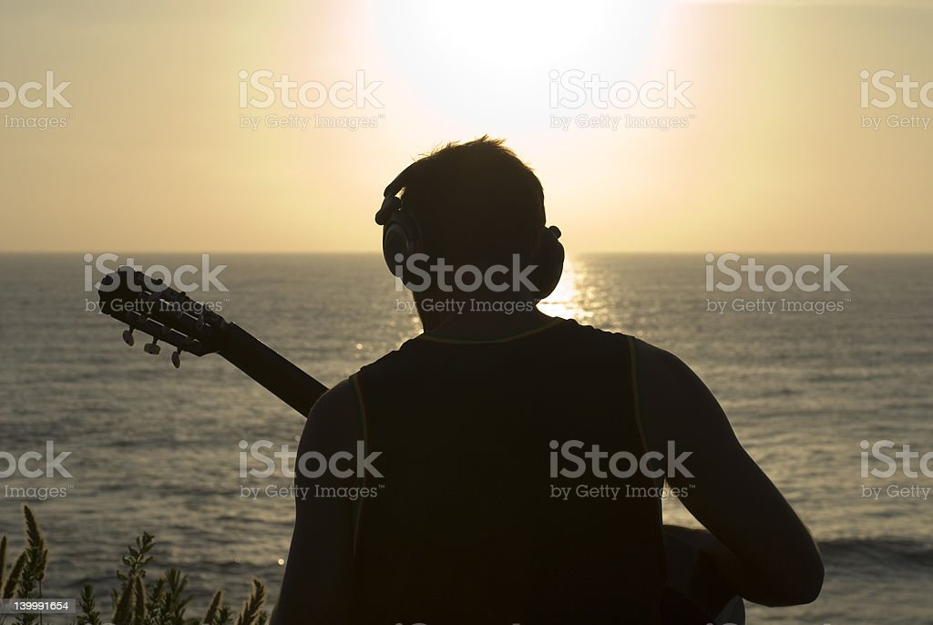 The Goodlife Young man on guitar watching the sunset, in La Jolla, CA. Acoustic Guitar Stock Photo