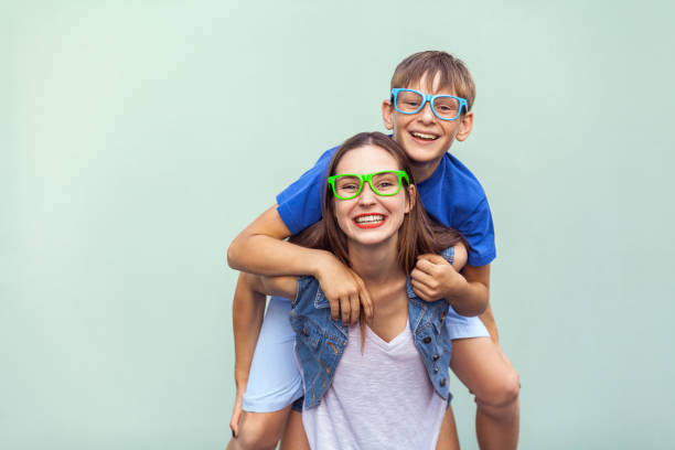 the gorgeous freckled brother and sister in casual t shirts wearing trendy glasses and posing over light blue background together. brother climbed up on the back of a cute sister. - older brother imagens e fotografias de stock