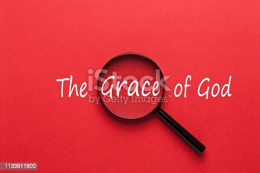 The Grace of God written on red background and magnifying glass.