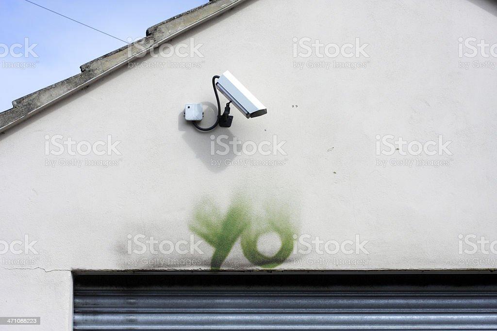 Mocking graffiti tag yo below security camera vandalism surveillance stock photo
