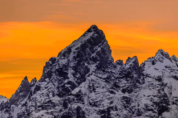 The Grand Ablaze The Grand Teton range is backlit with the vibrant sun setting behind it. ablaze stock pictures, royalty-free photos & images