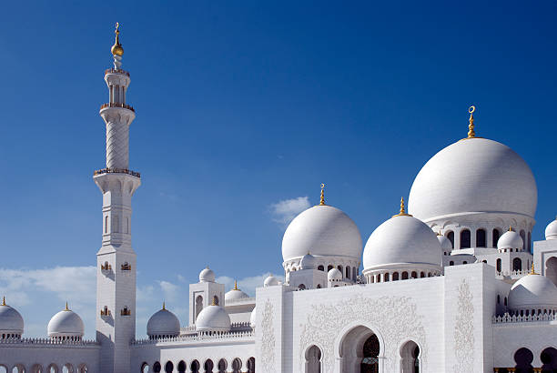 the grand mosque in abu dhabi with beautiful blue sky - moskee stockfoto's en -beelden