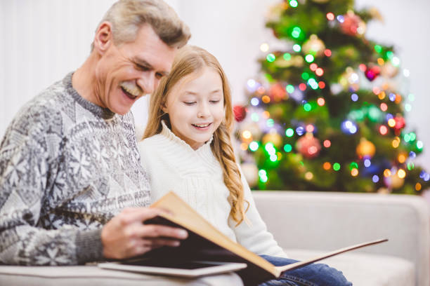 the granddaughter and a grandfather read the book near the christmas tree - holiday and invoice family foto e immagini stock