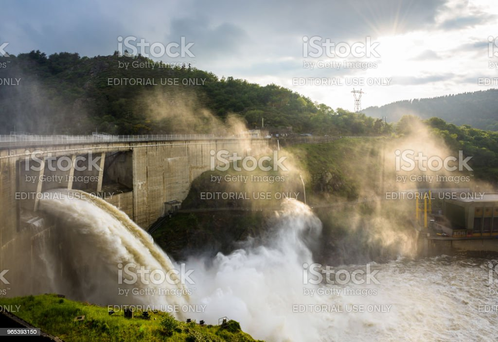 The Grangent dam, seen during a water release at sunset, is a concrete arch dam built in 1957 on the river Loire in the surroundings of Saint-Etienne. royalty-free stock photo