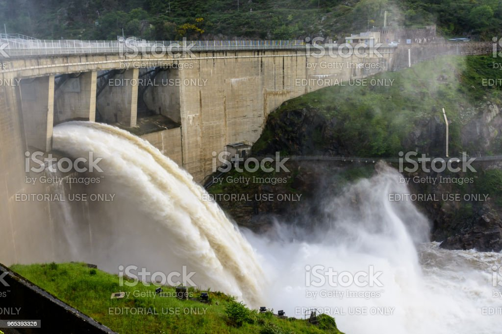 The Grangent dam, seen during a water release at sunset, is a concrete arch dam built in 1957 on the river Loire in the surroundings of Saint-Etienne. zbiór zdjęć royalty-free