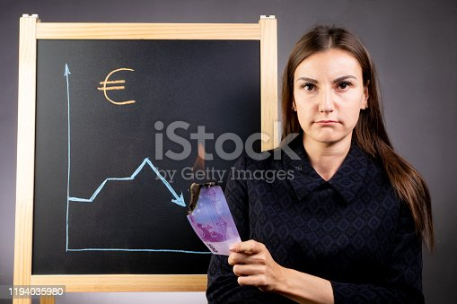 The graph of the fall of the euro is drawn on a black chalkboard, a sad woman is standing next to her and is holding a burning note in the amount of 100 euros. The foreign exchange financial market.