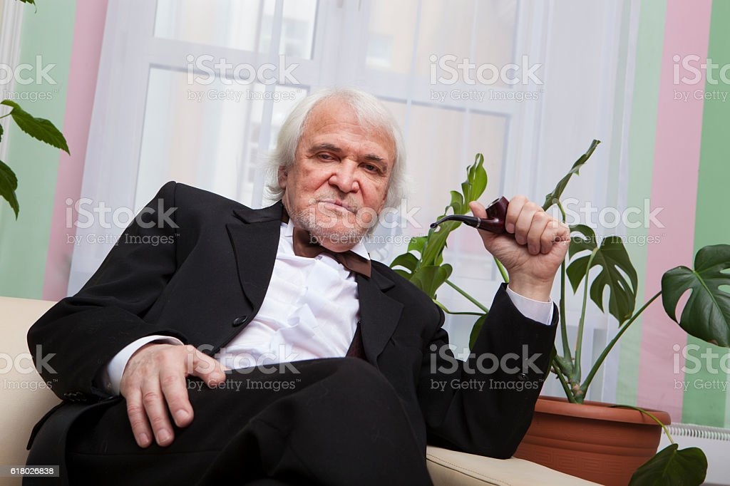 The gray-haired man in a tuxedo sitting on the couch stock photo