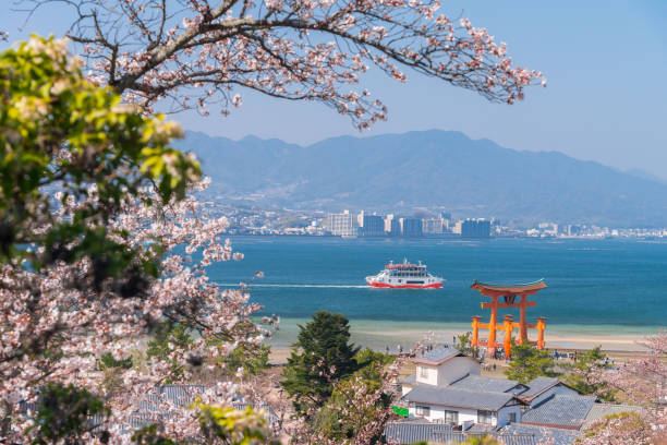 The Great Torii of Miyajima Island from mountain view with ferry ship HIROSHIMA,JAPAN:MARCH 28, 2018-The Great Torii of Miyajima Island, Hiroshima, Japan from mountain view with ferry ship miyajima stock pictures, royalty-free photos & images