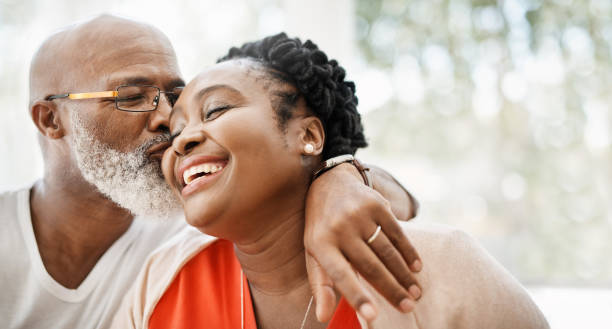 The greatest gift I ever got was you Shot of a mature man affectionately kissing his wife at home african american ethnicity stock pictures, royalty-free photos & images