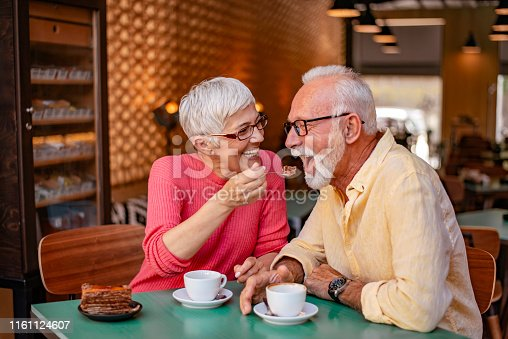 Senior couple dating in a bar-restaurant - Mature couple talking and having fun. Waist-up photo of pretty senior couple with smiles on their faces enjoying tea or coffee and chocolate pie. Wife feeding husband with a slice of cake.
