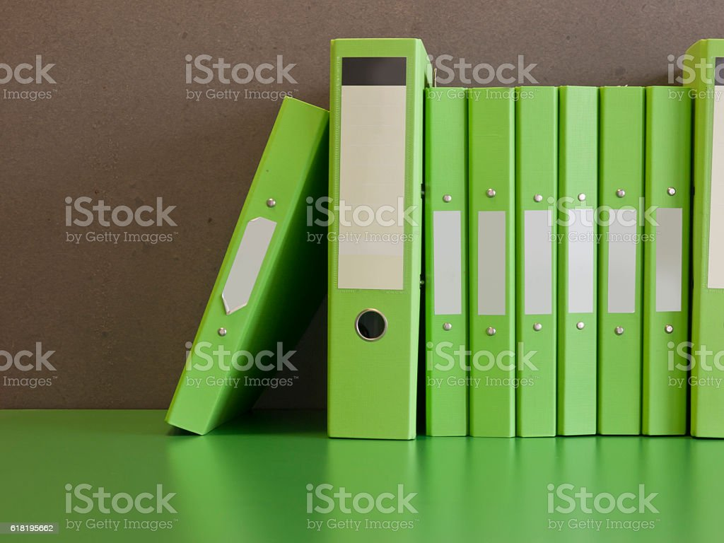 The row of green document files in front of the cement wall background