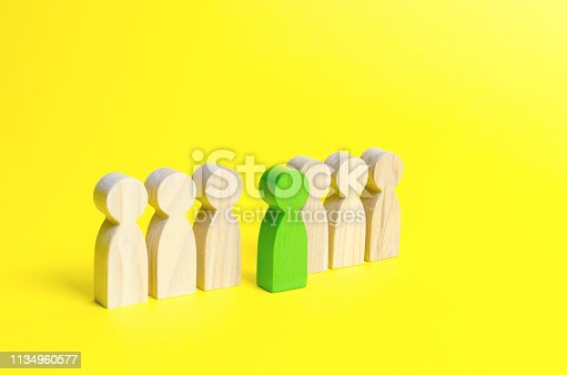 483424715 istock photo The green figure of a man comes out of the line of people on an yellow background. Talent, leader, professional. concept of success and improvement in work, the universal recognition of efficiency 1134960577