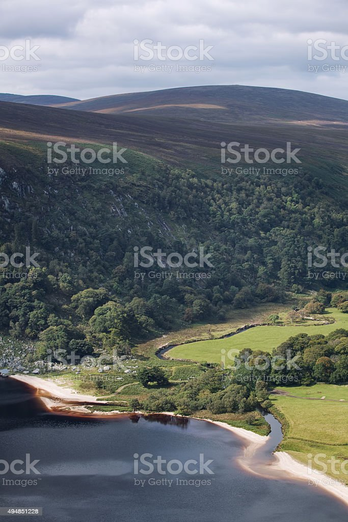 The green irish mountains next to a Guinness lake stock photo