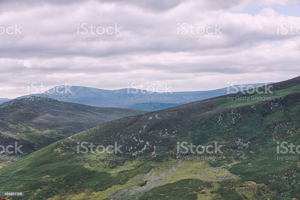 The green irish mountains with the baige cloudy sky stock photo