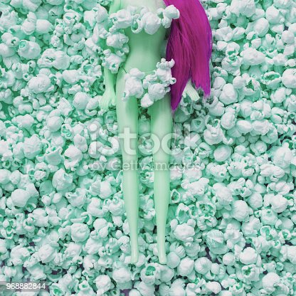 964258970 istock photo the green part of the plastic doll with pink hair lies among the popcorn. 968882844