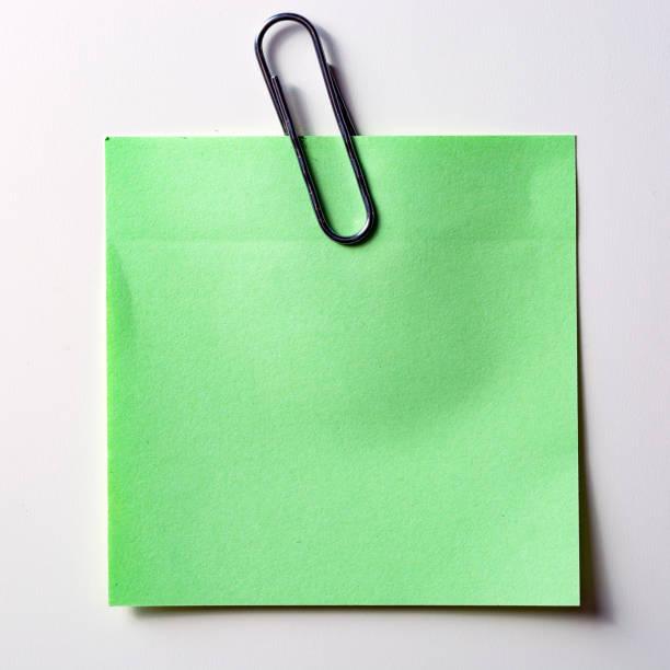 Die grüne Plakette mit einer gold Büroklammer, isoliert auf weißem Hintergrund – Foto