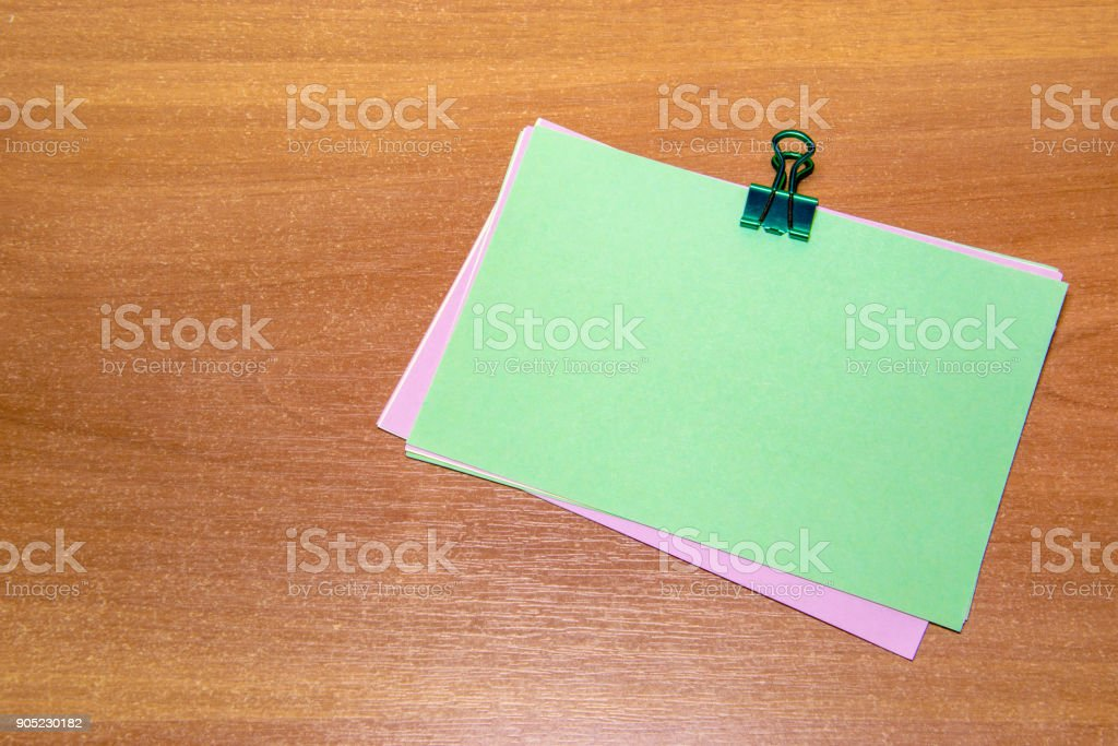 The green sticker with a paperclip, isolated on wooden background. stock photo
