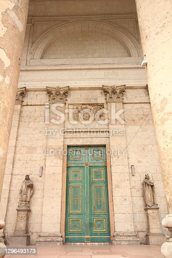 Esztergom, Hungary-June 27, 2013: The green wooden door of the Esztergom Basilica is decorated with yellow gilded paint over the door, there is a relief on it and a statue on both sides.