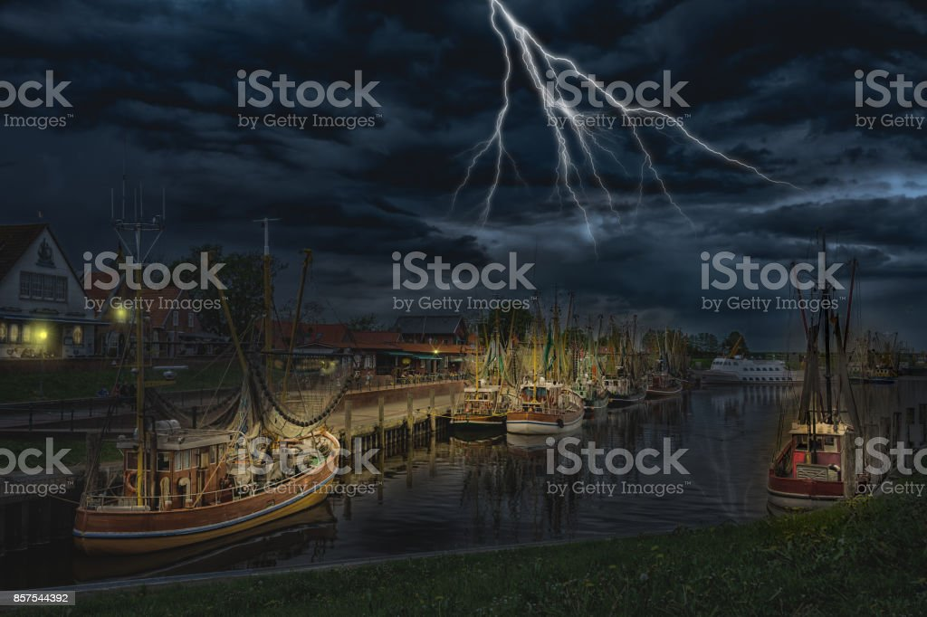 The Greetsiel harbor in the evening during thunderstorms stock photo
