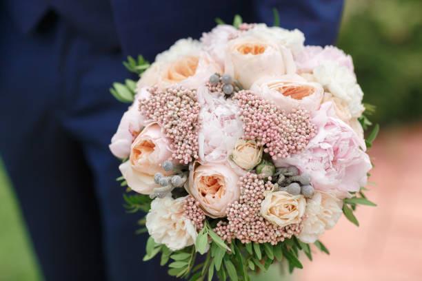 der bräutigam hält eine schöne hochzeit bouquet von pfingstrosen - brautstrauß aus holz stock-fotos und bilder