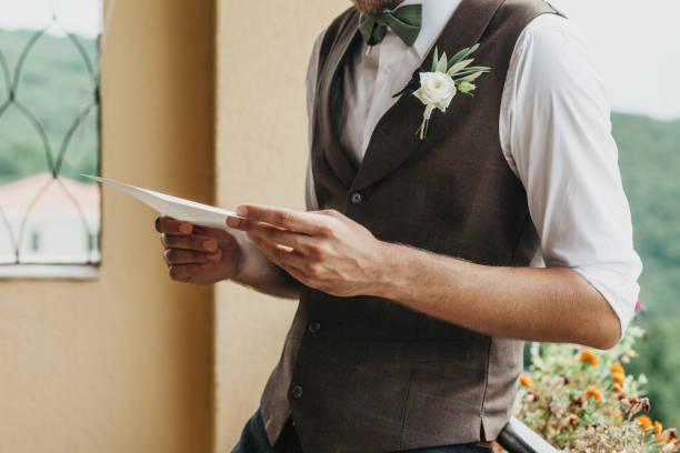 Der Bräutigam hält einen Eid in den Händen – Foto