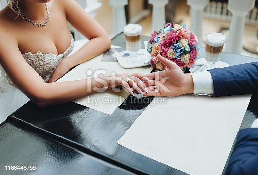 The groom holds the bride's hand in the cafe. Cups with cappuccino and bouquet from red rose. Wedding concept.