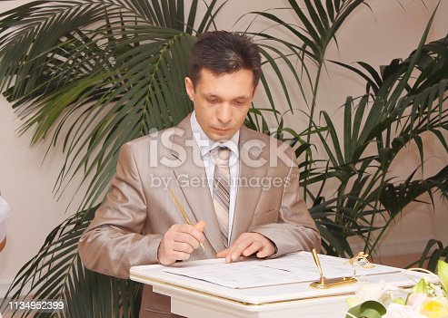 The groom in a wedding suit signs the marriage documents.