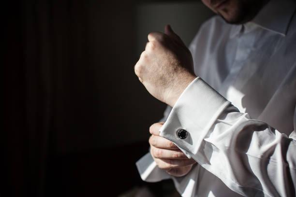 O noivo em uma camisa branca usa um botão de punho. - foto de acervo