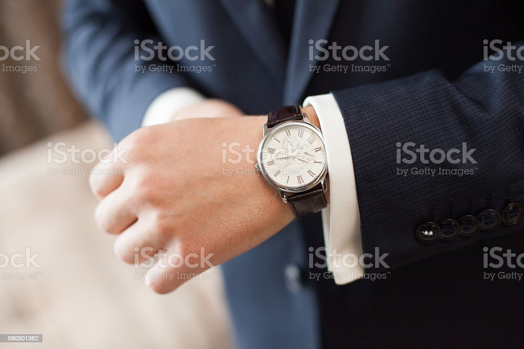 The groom in dark suit puts on a watch, closeup Стоковые фото Стоковая фотография