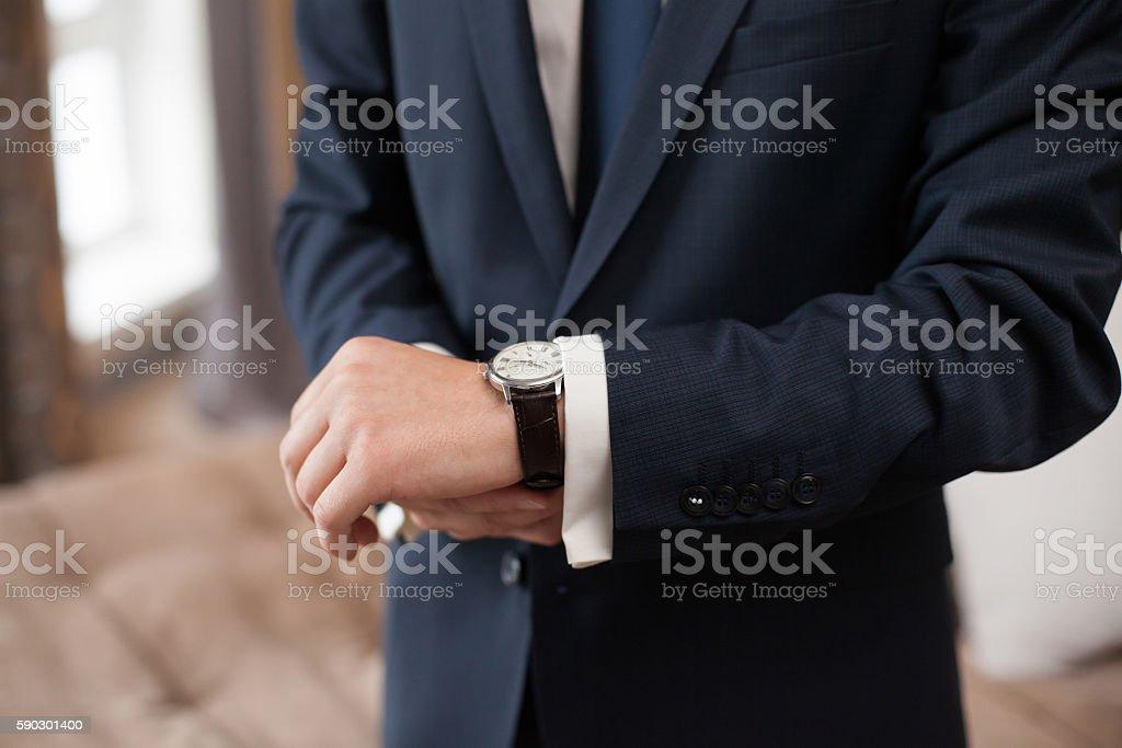 The groom in dark suit puts on a watch, closeup royaltyfri bildbanksbilder