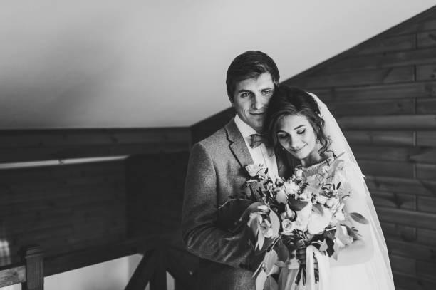 der bräutigam im anzug umarmt braut in weißem kleid halten eine schöne hochzeit blumenstrauß blumen, grün und mit band zu hause dekoriert. porträt eines schönen jungen paares. schwarz-weiß-foto. - bräutigam anzug vintage stock-fotos und bilder