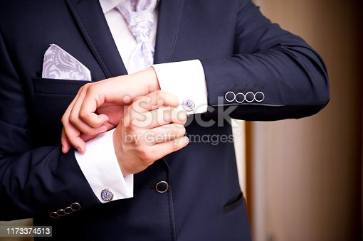 istock the groom pointedly straightens the cufflink on the shirt, close-up 1173374513