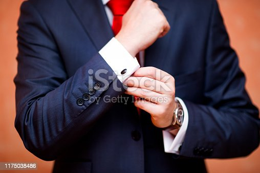istock the groom straightens the cufflink on the shirt, close-up 1175038486