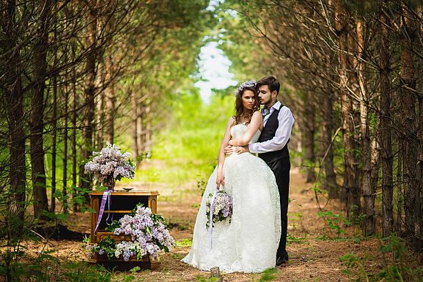 bräutigam mit der braut in das holz mit flieder - grüne wald hochzeiten stock-fotos und bilder