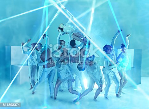 The group of modern ballet dancers on blue studio background