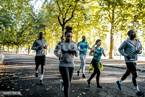 The group of running people in the park.