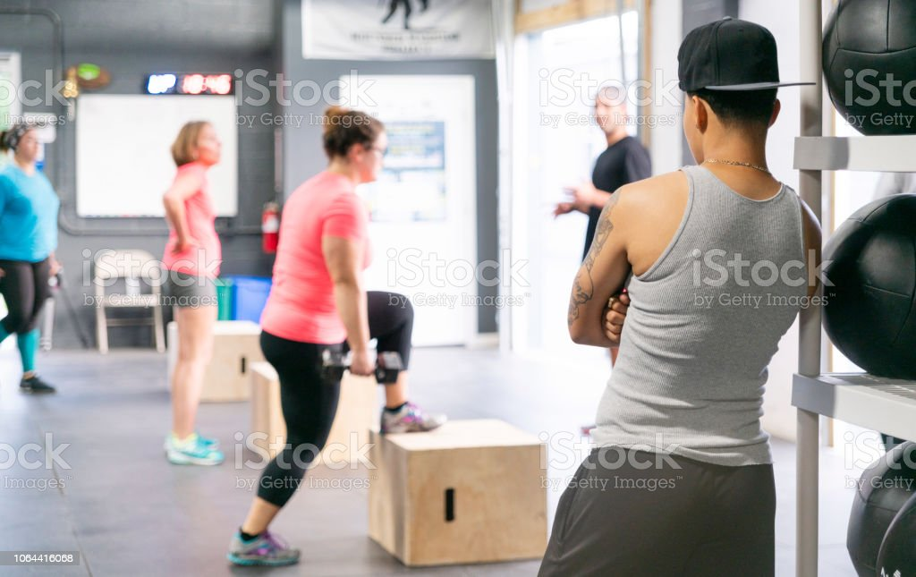 The group of women doing step-up exercise on the cubes in the gym, under the supervision of the male coaches stock photo