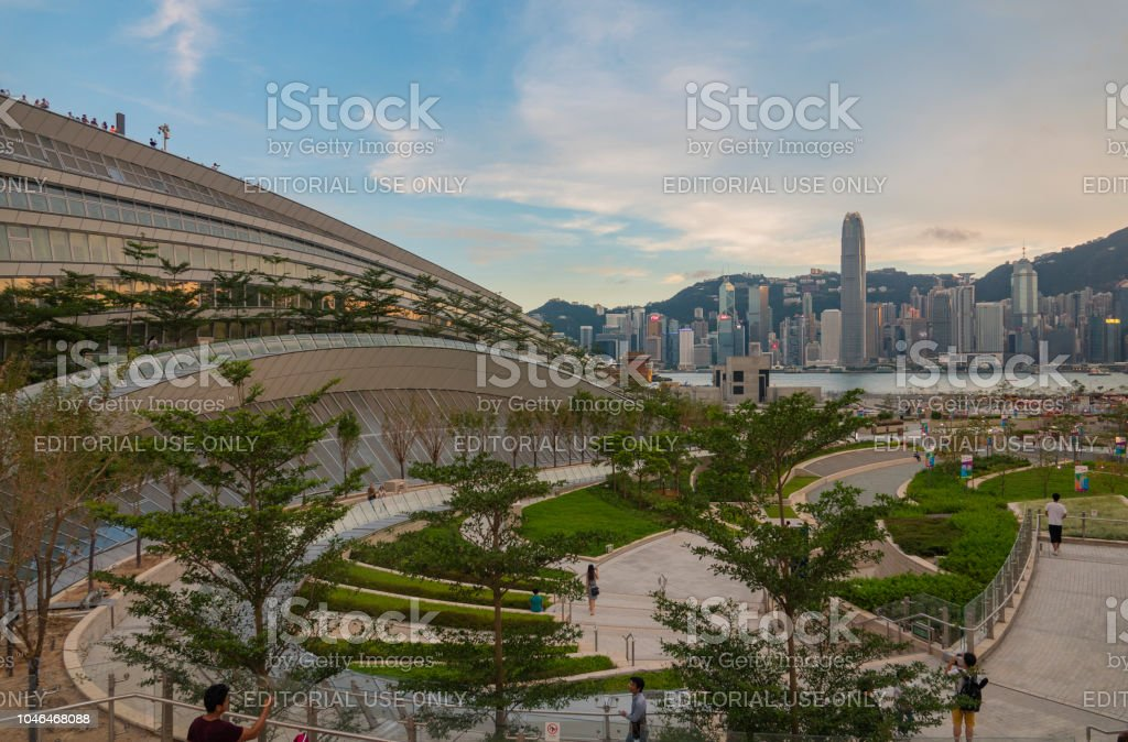 The Guangzhou-Shenzhen-Hong Kong High Speed Rail (Hong Kong Section) commences service September 23, 2018, Hong Kong: People are seen at the landscape deck and cultural plaza above the West Kowloon Terminus of Guangzhou-Shenzhen-Hong Kong High Speed Rail (Hong Kong Section) with a view of Victoria Harbour. The 26 kilometre railway, which commences today, links Hong Kong up to China's high-speed rail network, currently the world's largest, allowing passengers to travel from the city to Shanghai and Beijing. Beginnings Stock Photo