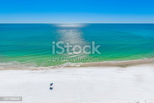 The emerald waters of the gulf of mexico at panama city beach, deserted except for colorful beach umbrella.
