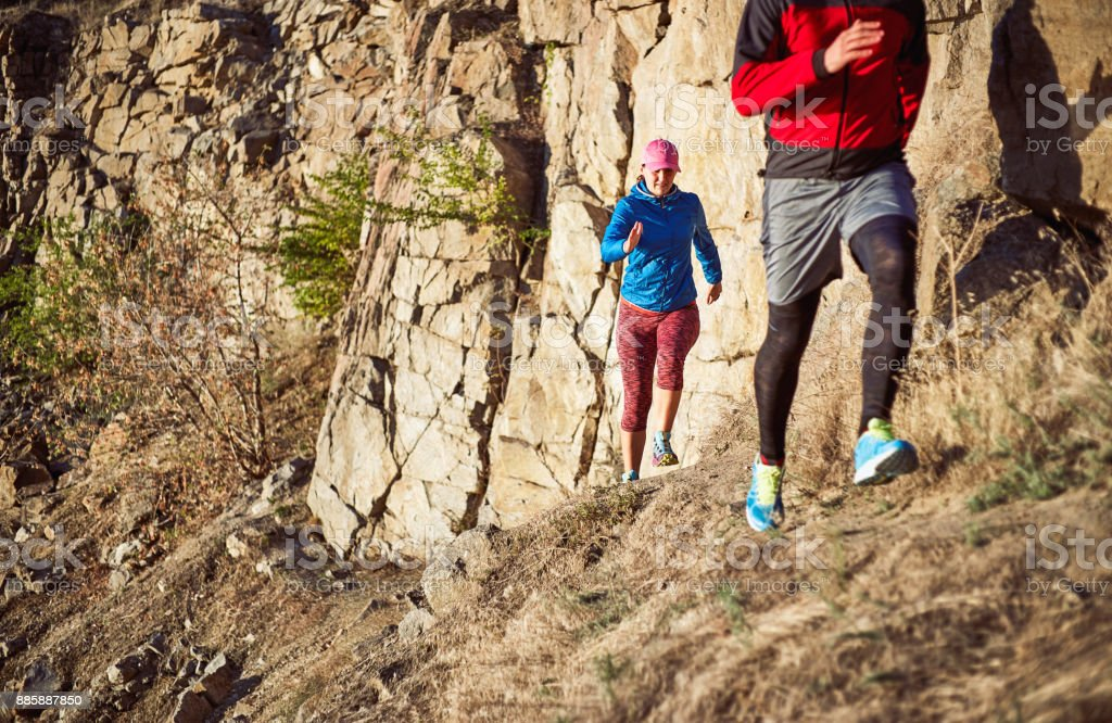 The guy and the girl are running along the path in the mountains. stock photo