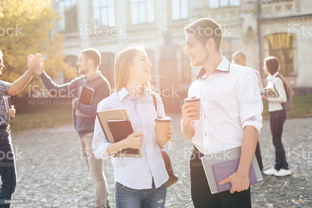 The guy and the girl are standing together in the courtyard of the university. stock photo
