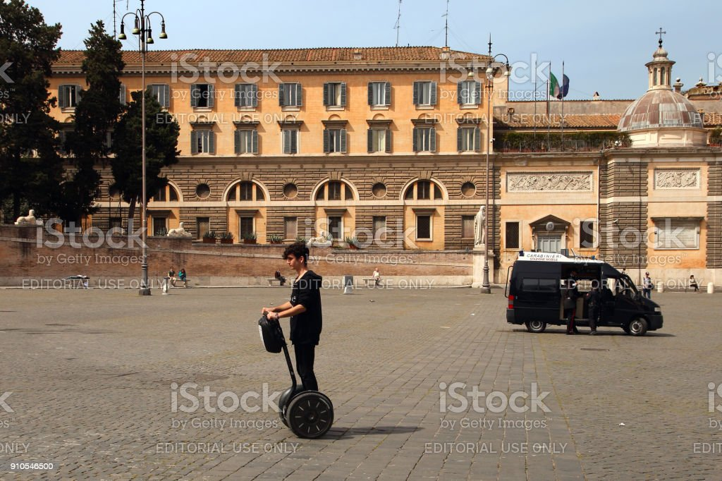 The guy crosses the square on the segway.  People's Square (Piazza del Popolo) with its fountain and obelisk in centre named after the church of Santa Maria del Popolo - is a large urban square in Rome. stock photo